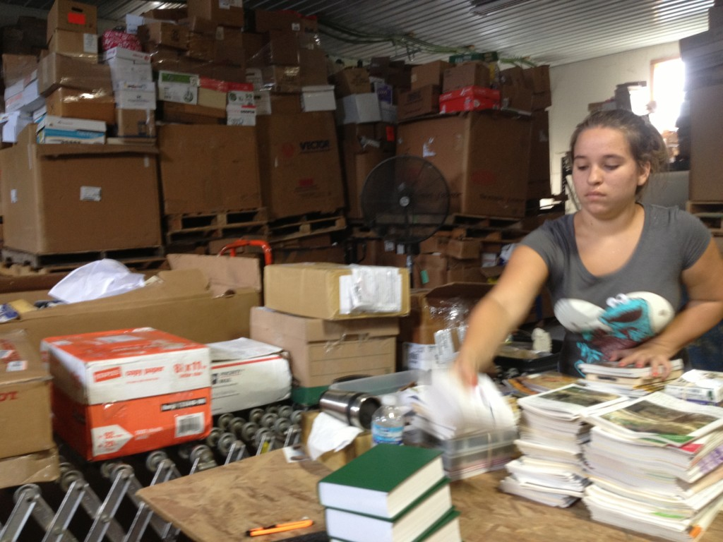 Sydney sorting donations. That's only a small part of the To Do pile behind her.